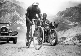 A cyclist climbing a mountain, followed by a motorcycle and a car.