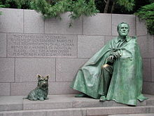 """""""A green statue of a man wrapped in a cloak alongside a statue of a Scottish Terrier."""""""