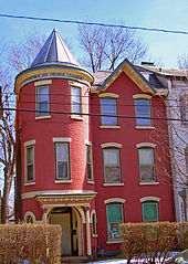 Narrow, red three-story house with turret