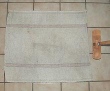 Un morceau de tissu en coton épais blanchâtre agrémenté de fines lignes colorées et une sorte de balais sans poils.