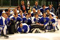 Photo de l'équipe féminine finlandaise qui pose avec un trophée dans la main de son entraîneur.