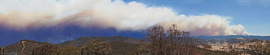 Panorama of a hilly expanse featuring a large smoke trail covering more than half of the visible sky.