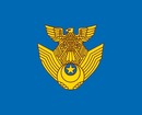 A golden symbol placed on a blue background. The golden symbol is an eagle perched on a pair of wings.