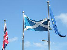 Union Flag, Scottish Flag and European Flag on poles against a blue sky.