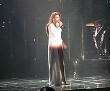 Cette image nous présente une femme brune afro-américaine qui porte une longue robe blanche mais elle a la jambe droite découverte. Elle porte des boucles d'oreilles et des talons blancs. Elle tient un microphone qu'elle porte à sa bouche avec la main gauche. Au second plan, à droite, il y a une personne avec une guitare électrique ou une basse.