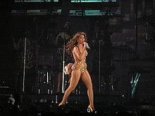 Une femme brune afro-américaine est en train de marcher et de chanter. Elle tient un microphone avec sa main droite. Elle est vêtue d'un justaucorps doré. Dans le fond, trois femmes qui portent la même robe sont visibles.