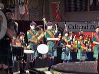 A group of eight young people wearing plaid kilts, green shirts, knee-high socks and navy berets stand on stage in a line, four playing bagpipes, four playing drums