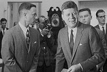Black-and-white film screenshot showing the main character on the left looking towards another man, President Kennedy, on the right. Kennedy is smiling and looking to his left. In the background several men are looking in different directions and one is aiming a camera.