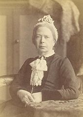 sepia photograph of a seated woman in conservative Victorian dress