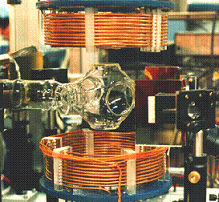 A complex experimental setup featuring a horizontal glass tube placed between two copper coils.
