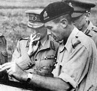 Three officers facing to the left looking at a document / map