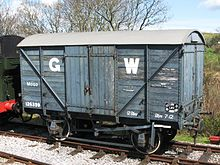 A short goods van built from planks of wood. The sides are mid-grey with a large white G to the left of the doors and a large white W to the right.