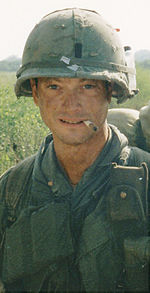 A man is at the center of the image looking at the camera. He is dressed in Vietnam War-era military attire including a vest and helmet. He has a cigarette sitting on his lips and is wearing a backpack.