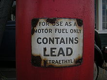 """a closeup of a red gas pump with a warning label that reads, """"for use as a motor fuel only"""" (in larger writing) """"contains lead"""" (in smaller writing) """"(tetraethyl)"""""""