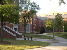 A red brick and white concrete, four-story apartment building with a landscaped courtyard in the foreground