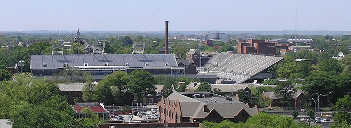 """An elevated view of several buildings and the trees surrounding them. A red brick building with a sloped roof is in the foreground, and a large white football stadium is just behind it, taking up much of the center of the picture. Beyond the stadium, there is a red brick smokestack near the center of the picture, the red brick Tech Tower building on the left side bearing white letters that spell """"TECH"""", and the red brick physics building on the right side. In the background there is a white domed building. All around these buildings are green-leafed oak trees. An overcast, light blue sky takes up the top third of the picture."""