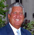 A portrait of a tan man with white-gray hair in a blue suit, smiling.