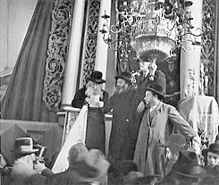 A sepia photograph shows a rabbi standing on the synagogue podium, addressing the congregation. He is reading from a sheet of paper, and three other men stand to his left. Behind him can be seen the white columns and ornate carvings of the holy ark. A chandelier, suspended from the ceiling, appears at the top right.