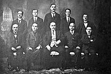 Photographie en noir et blanc représentant les écrivains, de face, sur deux rangs, ceux du premier étant assis, ceux du deuxième étant debout. Tous sont en costume cravate sauf Dun Karm Psaila qui porte l'habit de prêtre et la croix.