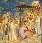 The wise men and several animals cluster around the baby Jesus, while a comet-like object streaks overhead