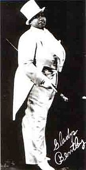 A publicity photo of a stout African American woman in white tuxedo with tails and top hat, carrying a cane and her signature in the lower right corner