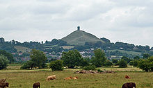 A mound surmounted by a tower in the distance. In the foreground are fields with cows and small trees and bushes.