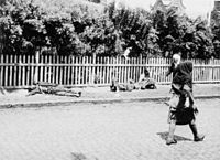Passers-by ignore corpses of starved peasants on a street in Kharkiv, 1933.