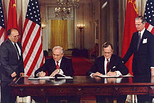 Two men in suits sit signing documents at a large table in front of their country's flags. Two others stand outside watching them.