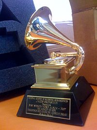 A gold gramophone trophy with a plaque set on a table
