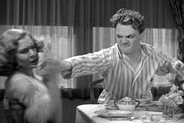 Cagney is in stripped pajamas. He looks angry as he reaches across a breakfast table with the grapefruit in his hand.