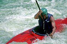 Man wearing helmet sitting in fiberglass boat, paddling through frothy water