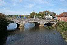 A stone three arch bridge over water. On the bridge is a small blue lorry. Either side of the river is vegetation and to the right of the bridge houses.