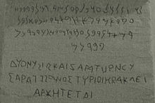 Agrandissement de l'inscription bilingue gréco-phénicienne se trouvant sur la base du cippe présenté ci-avant. Le phénicien est au-dessus, le grec en-dessous, gravé en capitales permettant de bien distinguer la présence des voyelles qui furent créées par les Grecs.