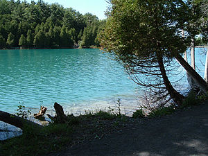 """Green Lake, seen from its eastern shore. The lake&squot;s unusual blue-green color is due to annual """"whitings"""" that leave suspended mineral solids in its water.[1] The mineral content of the water also makes the lake meromictic, which is quite rare and which has led to intense scientific study of the lake for nearly a century."""
