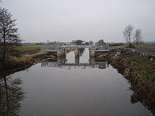Straight watercourse, surrounded by fields and crossed by metal and concrete structure.