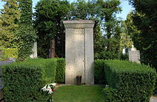 """A tall stone column bearing the words """"Gustav Mahler"""", surrounded by a low green hedge, with a floral bloom in the foreground"""