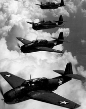 Black-and-white aerial shot of four planes (with white stars on each wing and the body) flying in formation adjacent to each other over clouds.
