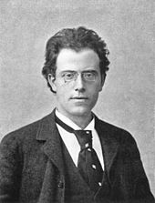 Young dark-haired man wearing a loose necktie with a white shirt and a dark jacket