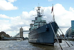 The bow of a large blue warship, moored on a river, with a bridge in the background.