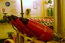"""""""A circular rack of conical shells. The shell cases are red, the rest of the room is white."""