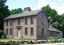 The main part of the home is a wooden, 2 1⁄2-story rectangular building with large windows, one central door, and a central chimney. A smaller wing extends back from the right side. There are large trees in the background and a low rock wall in the foreground.[75]