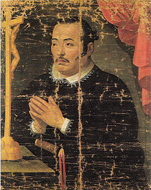 Painting of an Asian man in black priest robes with white collar praying in front of a crucifix.