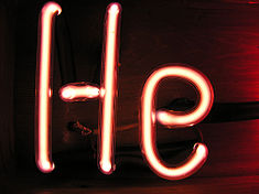 Illuminated light red gas discharge tubes shaped as letters H and e
