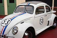 A white Volkswagen Beetle with a racing stripe across the middle and the number 53 on the front and the door
