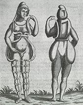 A front and back illustration of a Renaissance-era hermaphrodite showing a person with female facial features, breasts, and what appears to be a small penis or large clitoris. She wears a small hood and open robe tied multiple times around the legs. Where it opens in the front, the apparent rear appearance shows it to be perhaps a shell of some kind, as one with her body Two squares are missing from her the back of her head and torso. She has no buttocks.