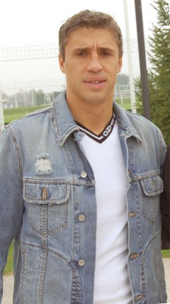 A man dressed in denim jacket and white t-shirt stands outside a football training pitch.