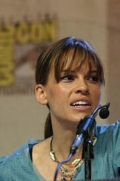 Hilary Swank regarde vers sa gauche pour écouter quelqu'un, elle est face à un micro durant le Comic-Con de San Diego