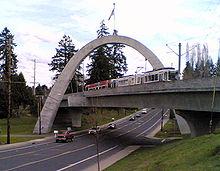 A MAX light rail train crossing the Main Street Bridge. The bridge is a tied concrete arch structure.
