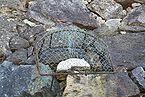 """Photo of the """"old widow&squot;s stone"""" covered with a wire net"""