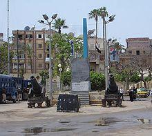 """Photo of a public square in Rashid (Rosetta) in Egypt featuring a replica of the Rosetta Stone"""